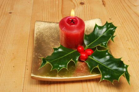 Burning red candle and holly with berries photo