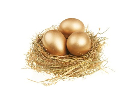 nest egg: Three golden eggs in a nest of straw