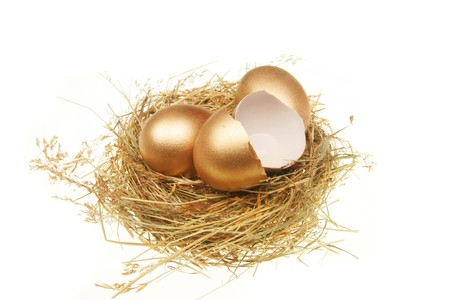 Two whole and one broken golden eggs in a straw nest Stock Photo