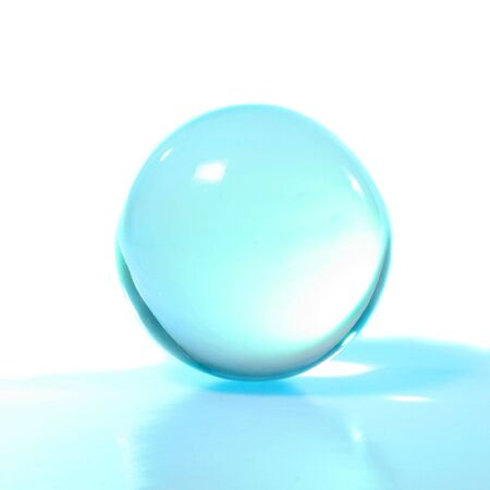 Turquoise crystal ball with reflection against white