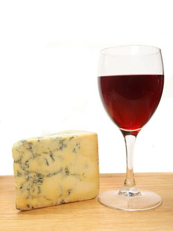 stilton: Glass of red wine and stilton cheese on a board