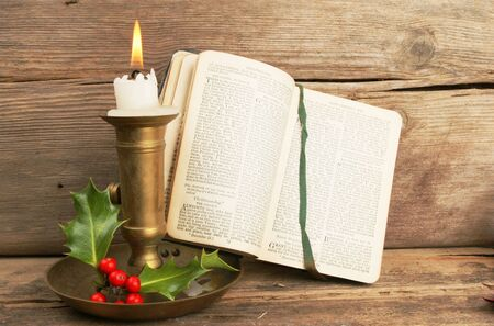verse: Antique prayer book open on a Christmas prayer lit by candle light Stock Photo