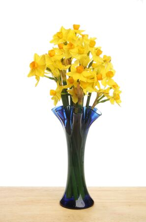 Arrangement of Soleil daffodil flowers in a vase on a wooden board photo
