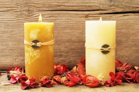 Two burning feng shui candles with dried flowers on a background of old wood Stock Photo - 7271332