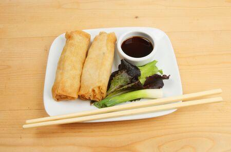 Chinese pancake rolls, salad garnish and chopsticks on a plate photo