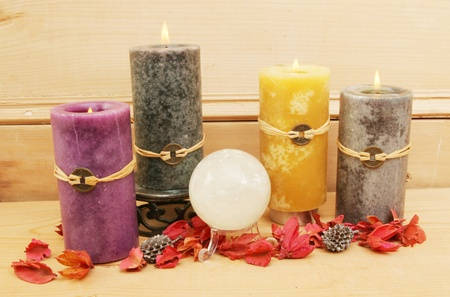 Four Feng-Shui candles with a crystal ball and potpourri against an old pine panel Stock Photo - 8997638