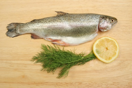 Fresh whole rainbow trout with dill herb and a slice of lemon on a wooden food preparation board Stock Photo - 9651924