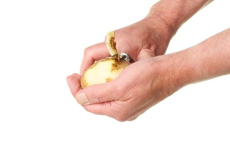 Male hands peeling a potato isolated against white Stock Photo - 10437794