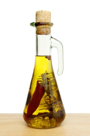 flavoured: Flavoured olive oil in a glass jar on wood against a white background