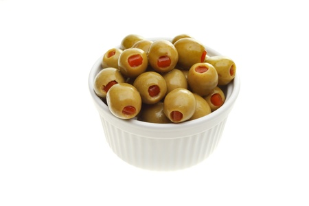 pimento: Pimento stuffed green olives in a ramekin isolated against white