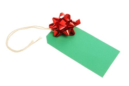 Blank green Christmas gift tag with a red foil bow Stock Photo