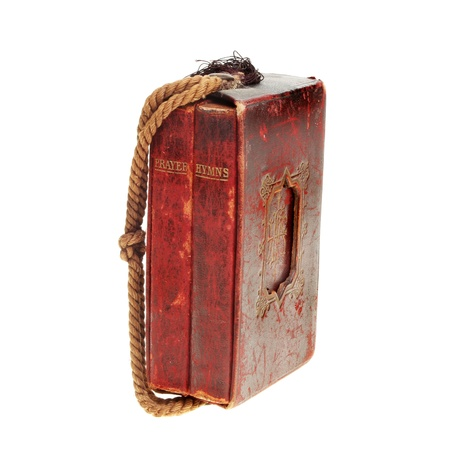 hymn: Antique red leather bound prayer and hymn books in a case with a cord handle isolated against white Stock Photo