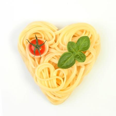 Gesundes Essen, Spaghetti in einer Herzform mit Tomaten und Basilikum auf wei�em Hintergrund