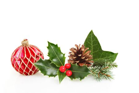 Christmas seasonal foliage and red and gold glitter decoration against a white background