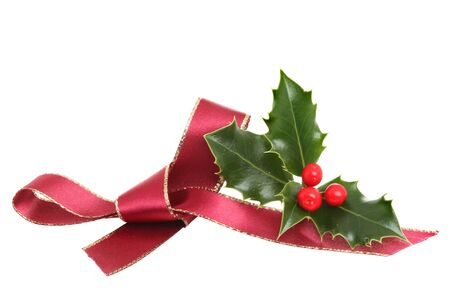 Red ribbon bow and a sprig of fresh holly with ripe berries isolated against white