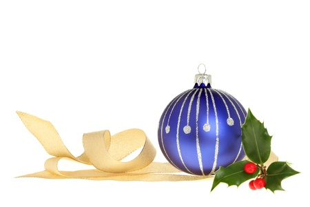 Christmas decoration of blue bauble, gold ribbon and a sprig of holly with red berries isolated against white Stock Photo - 11158103
