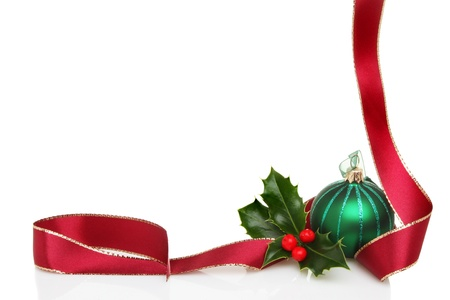christmas border: Christmas border or frame of red ribbon, green glass bauble and fresh holly leaves with berries, white copy space Stock Photo