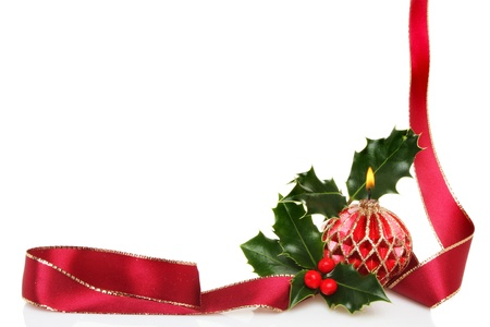 A Christmas frame of red ribbon, a burning decorative candle and fresh holly with white copy space photo