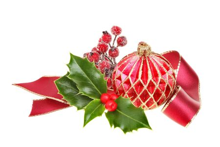 Christmas decoration a red and gold glitter bauble gold edged red ribbon, frosted berries and a sprig of fresh holly isolated against white Stock Photo - 11254608