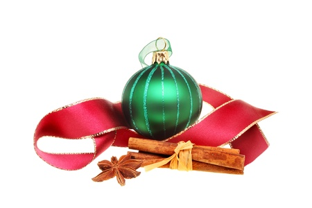 christmas motif: Christmas motif, green glass bauble with a gold edged red ribbon, cinnamon and star anise spices isolated against white