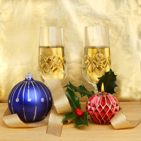 Christmas themed still life of champagne in glasses decorations and a burning decorative candle against a gold background photo
