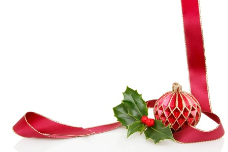 A Christmas themmed frame or border of a red and gold bauble, ribbon and a fresh holly sprig, white copy space in center photo
