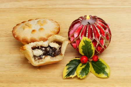 Mince pies with a burning decorative candle and a sprig of fresh variegated holly on a wooden board photo