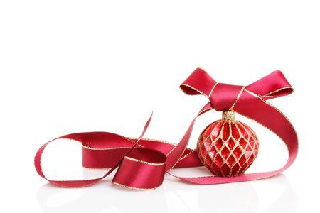 curled edges: Decorazioni di Natale un oro bordato nastro rosso con un fiocco arricciato intorno ad un rosso decorativo e bauble oro con riflessi morbidi su uno sfondo bianco