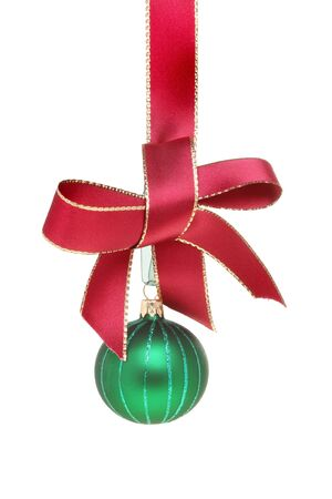 Green Christmas bauble hanging from a gold edged red ribbon tied with a bow isolated against white Stock Photo