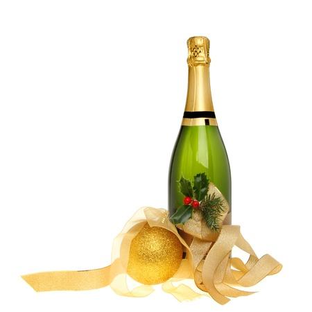 Kerst champagne fles versierd met hulst, gouden linten en een gouden bal geïsoleerd tegen witte Stockfoto