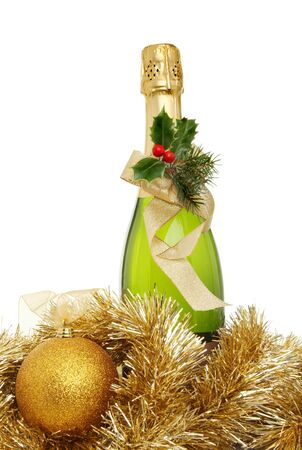 Christmas champagne, a bottle of champagne decorated with holly and a ribbon surrounded by tinsel and a golden bauble photo