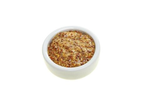 wholegrain mustard: Wholegrain mustard in a ramekin isolated against white