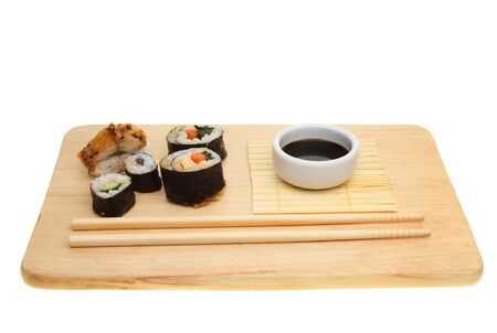 Japanese sushi,soy sauce and chopsticks on a board isolated against white photo