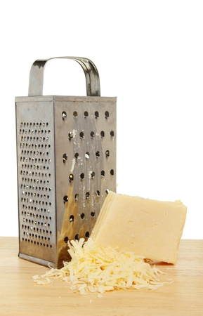 grater: Cheese grater and cheddar cheese on a wooden board Stock Photo