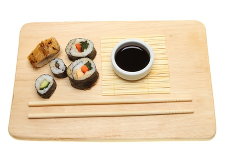 Japanese sushi, soy sauce and chopsticks on a board photo
