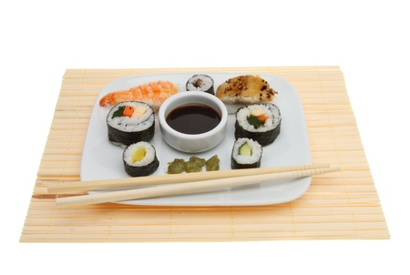 Group of mixed sushi on a plate upon a bamboo matt with chopsticks isolated against white photo