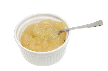 Apple sauce with a spoon in a ramekin isolated against white