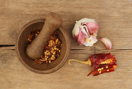 Chilli flakes in a pestle and mortar with garlic and cut chilli pepper on an old weathered wooden board photo