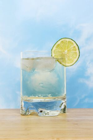 Cool and refreshing lime flavored drink on a wooden surface against a blue sky Stock Photo - 13553418