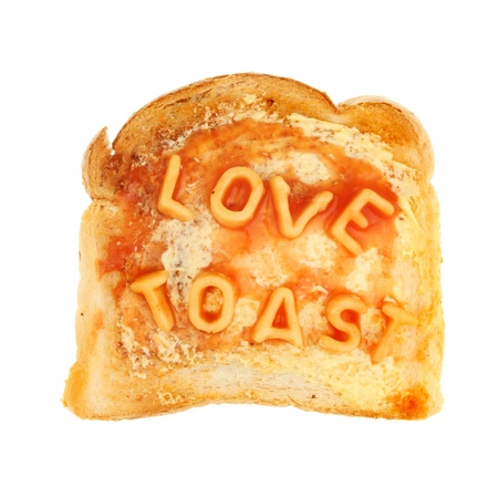 Alphabet spaghetti on buttered toast spells love toast isolated against white photo
