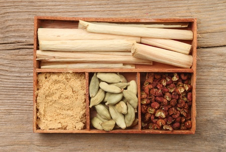 Herbs and spice,lemon grass,ground ginger,cardamom seeds and pepper corns in a wooden tray on a background of weathered wood photo