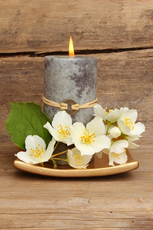 Burning Feng Shui candle and white philadelphus flowers on a gold dish against a background of weathered wood Stock Photo - 14270390