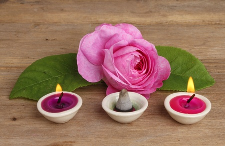 Pink rose with small burning candles and incense on a background of weathered wood photo
