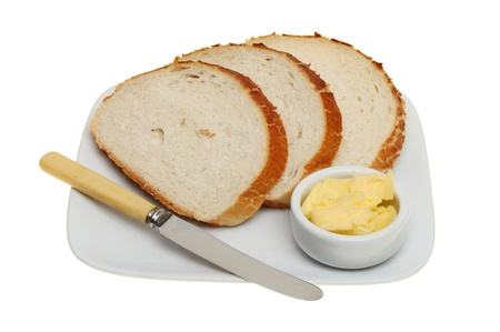 Slices of giraffe bread on a plate with a knife and a ramekin of butter isolated against white