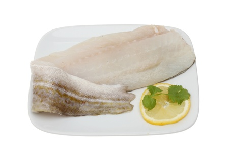 Fresh raw cod fillet with lemon and parsley garnish on a plate isolated against white photo