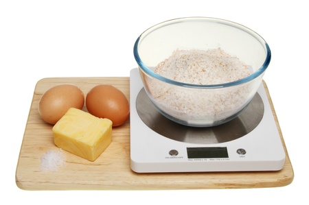 Eggs butter salt and flour on a weighing scale isolated against white Stock Photo