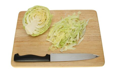 Cut white cabbage with a knife on a wooden chopping board isolated against white Stock Photo - 15148147