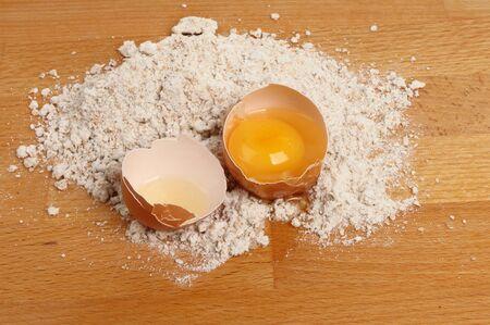 worktop: Cracked egg and wholegrain flour on a wooden kitchen worktop