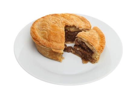 Meat pie on a plate with a slice cut out isolated against white Stock Photo