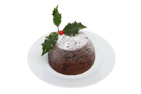 christmas pudding: Christmas pudding on a plate decorated with holly and dusted with icing sugar isolated against white